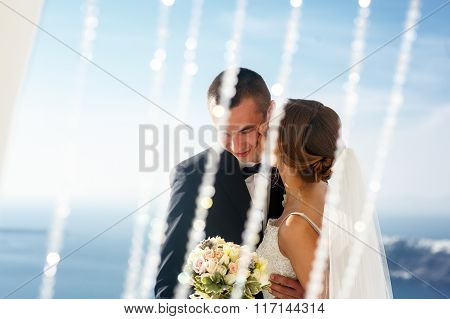 Beautiful Bride Kissing Happy Handsome Groom With Sea And Sky In Background