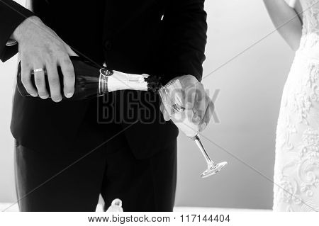 Groom Opening Champagne At Wedding Aisle Tent Sea Background Closeup B&w
