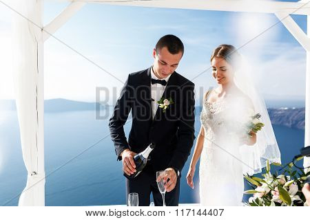Groom And Bride Opening Champagne At Wedding Aisle Tent Sea Background