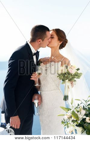 Newlywed Couple Drinking Champagne In Glasses And Kissing Closeup Sea Background