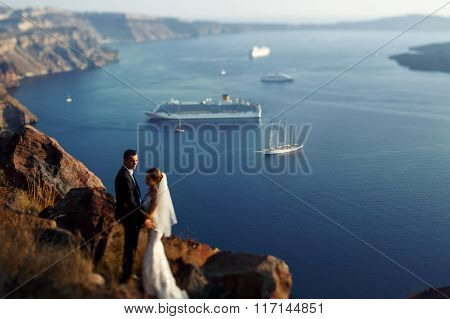 Bride And Groom Hugging At Sunset At Mountain Sea And Ships Background