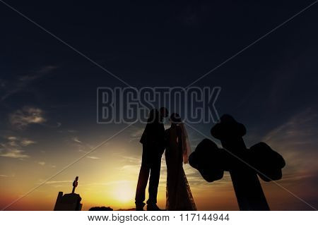 Handsome Groom And Beautiful Bride Kissing On Church Roof At Sunset Sky Background