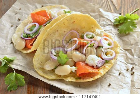 Tortilla tacos with vegetables: pumpkin, white beans, goat cheese and onions