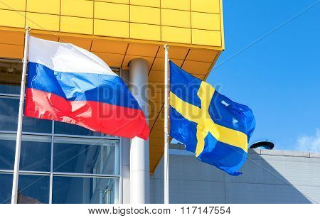Flags Of Sweden And Russia Waving Against Ikea Store