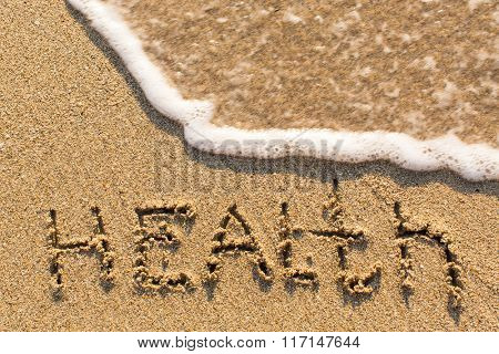 Health - inscription on sand beach with the soft wave.