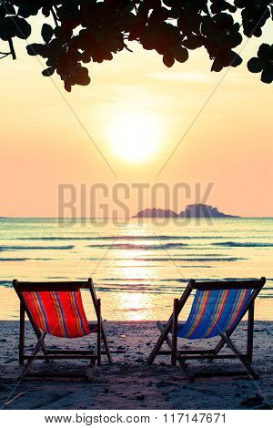 Pair of lounge chairs on sunset at beach.