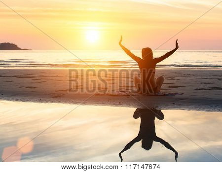 Silhouette of woman doing exercise at sunset on the beach with reflection in the water.