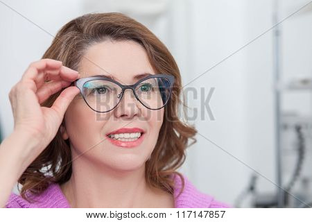 Cute lady is trying on eyewear in clinic