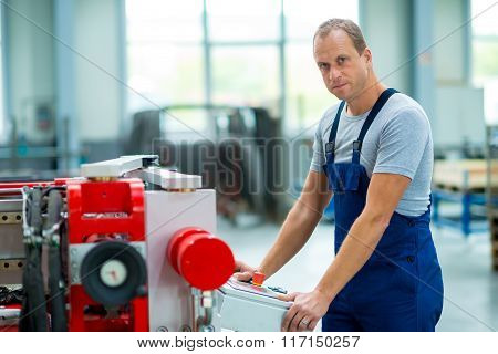 worker in industrial factory using machine