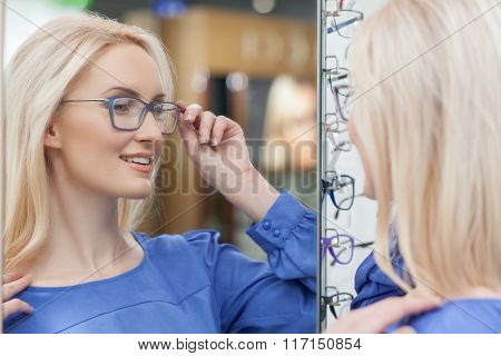 Cheerful young woman is selecting new spectacles