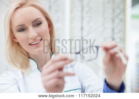 Pretty female ophthalmologist is showing new glasses