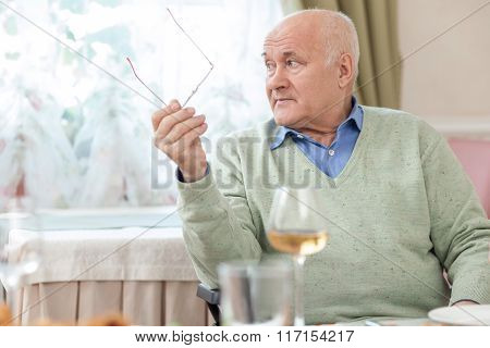 Cheerful old grandfather is resting in restaurant