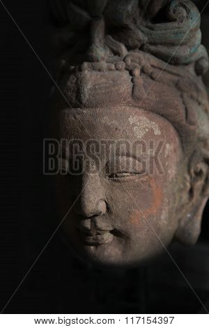 Buddha head statue in shadow