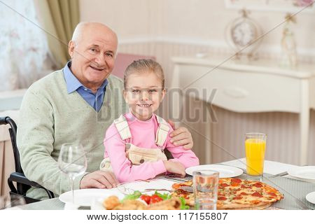 Cheerful grandparent has lunch with a child