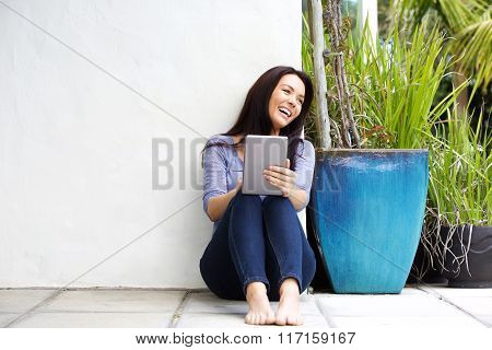 Smiling Woman Sitting In Patio With A Digital Tablet