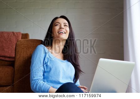 Smiling Young Woman Relaxing At Home With A Laptop