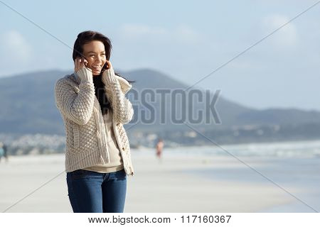 Cheerful Young Lady Using Mobile Phone On The Sea Shore