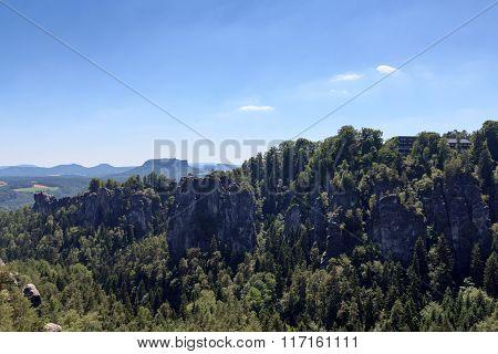 Panorama With Rocks Bastei, Table Mountain Lilienstein And Hotel In Rathen, Saxon Switzerland