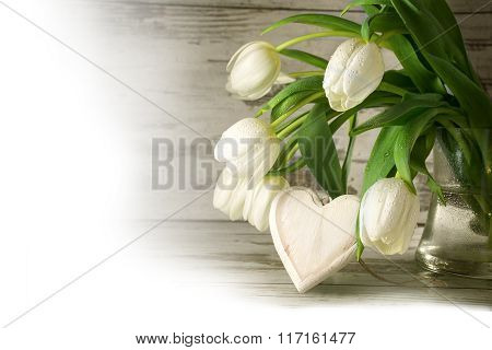 White Tulips And A Wooden Heart Shape Against Gray Wood, Corner Background Fades To White, Love Conc