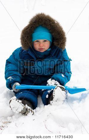 Cute Boy Sitting In Snow Outdoor