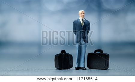 Miniature people - a businessman waiting in the airport lobby