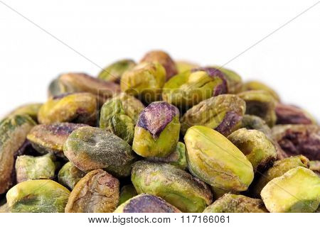 Pile of shelled pistachio nuts, over white background.