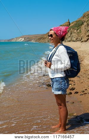Girl Stands On The Sandy Shore With A Backpack And Looking At The Ocean. Side View