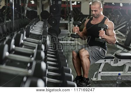 bodybuilder working out with bumbbells weights at the gym