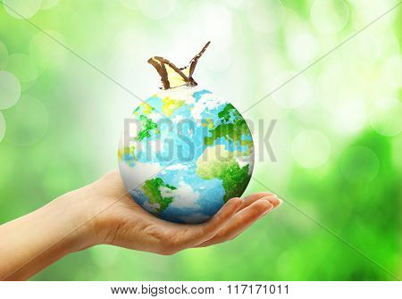 Globe on female human hand with butterfly in blur nature bokeh background with spfing leaves. Environment eco concept