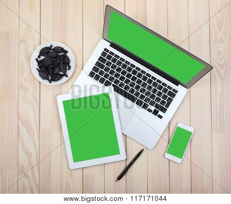 Open notebook, digital tablet and smart phone with saucer of candies on wooden background, top view