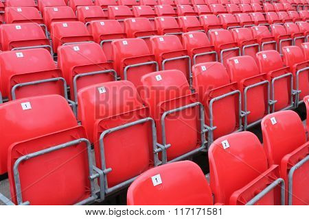 row of Red empty stadium seats with numbers
