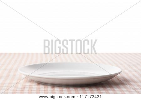 Empty White Ceramic Plate On Checkered Tableclot