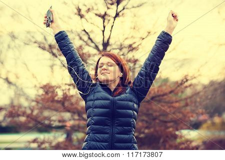 Young womanlistening to music breathing fresh air before a run