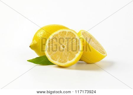 whole and halved lemons on white background