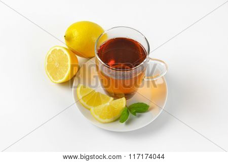 cup of black tea with lemon on white background