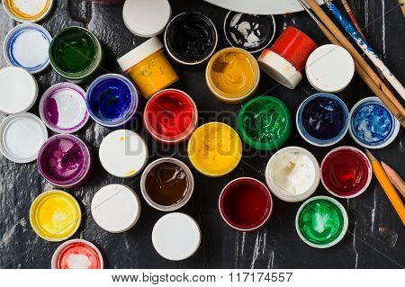 Different  Colors In The Banks, Pensils And Brushes  On The Floor