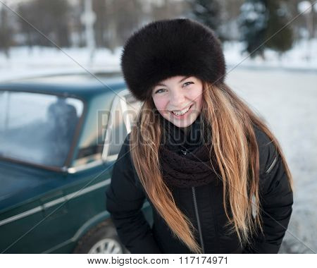 A smiling girl in a park in winter