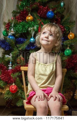 Little Girl Dreamily Looking Up On Chair Near Christmas Tree