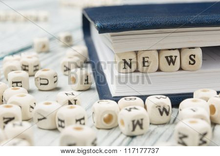 Wood blocks with  letters spelling news. Wooden ABC.