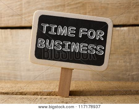 Chalkboard with Time For Business word on wooden background.