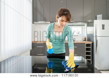 Asian Young Woman Cleaning Modern Kitchen At Home