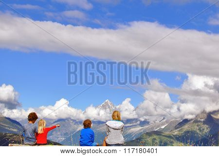 Kids Sitting At Viewpoint In Mountains