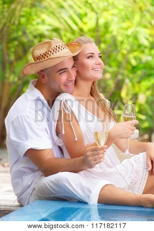 Two people in love sitting near swimming pool on the beach resort and drinking champagne, romantic honeymoon vacation