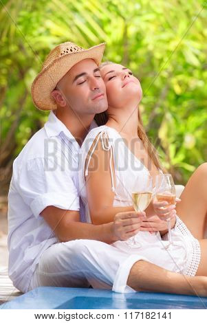 Gentle couple with closed eyes of pleasure sitting near the pool on tropical resort, drinking champagne on the beach, romantic summer vacation