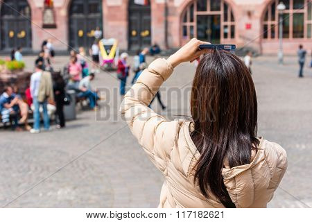 Back Side Of Young Woman Taking A Photo With Her Phone