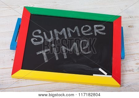 Blackboard with text it's summer time on wooden deck