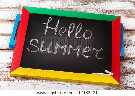 Blackboard with text it's hello summer on wooden deck