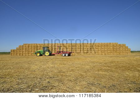 John Deere tractor parked in front of a huge straw stack