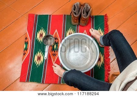 Woman Warms Her Feet In A Basin Of Water