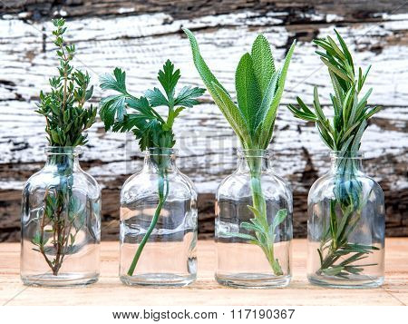Bottle Of Essential Oil With Herbs Rosemary, Sage,parsley  And Thyme  Set Up On Old Wooden Backgroun